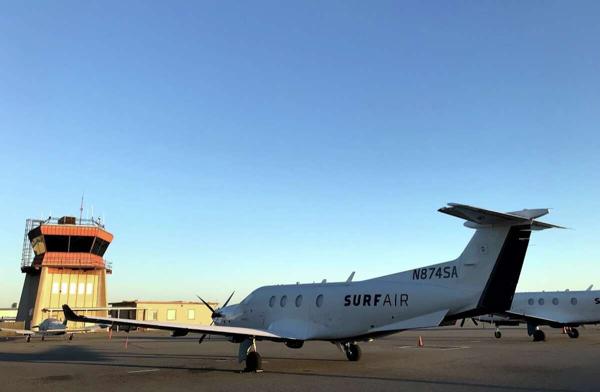 A Surf Air Pilatus PC-12 in front of the San Carlos airport tower