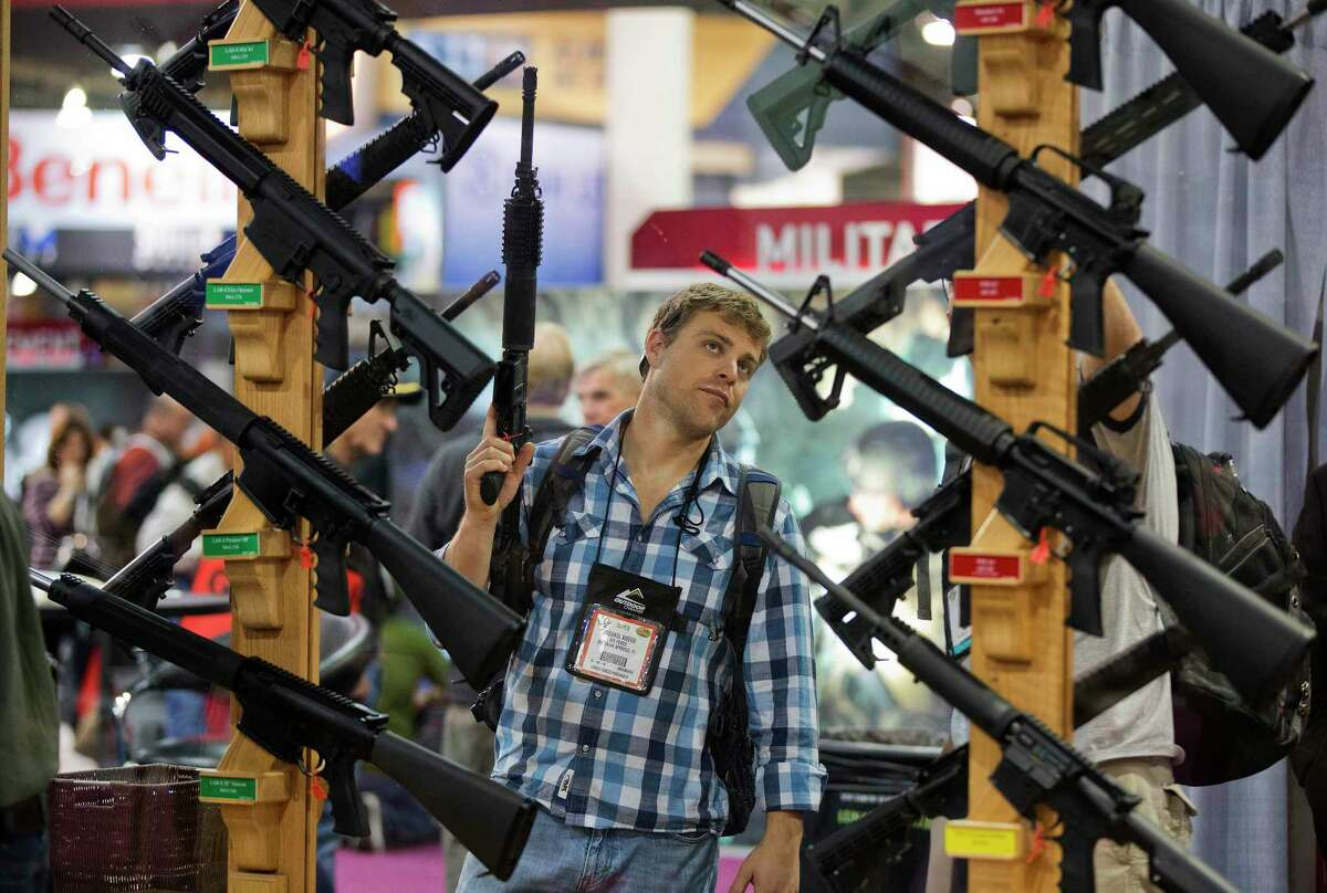 FILE - In this Jan. 17, 2013, file photo, Michael Kiefer, of DeFuniak Springs, Fla., checks out a display of rifles at the Rock River Arms booth during the 35th annual SHOT Show in Las Vegas. The largest gun industry trade show will be taking place in Las Vegas Jan. 23-26 just a few miles from where a gunman carried out the deadliest mass shooting in modern U.S. history. (AP Photo/Julie Jacobson, File)