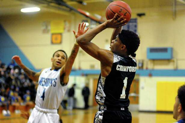 Bassick's Kevin Crawford lines up a shot as Harding's Zamir Hairston defends during basketball action in Bridgeport, Conn., on Tuesday Jan. 23, 2018.