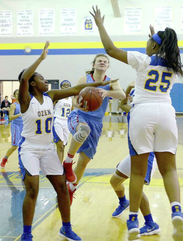 Ozen's #10 Haynes and #25 Gipson defend as Lumberton's #11 Wilkinson heads up to the basket during their District 22 - 5A match-up Tuesday at Ozen. Both teams are currently leaders in the district.  Photo taken Tuesday, January 23, 2018 Kim Brent/The Enterprise Photo: Kim Brent / BEN