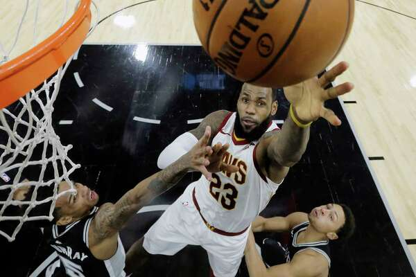 Cleveland Cavaliers forward LeBron James (23) shoots past San Antonio Spurs guard Dejounte Murray (5) and San Antonio Spurs guard Bryn Forbes, right, during the first half of an NBA basketball game, Tuesday, Jan. 23, 2018, in San Antonio. James passed the 30,000 career points mark in the first quarter. (AP Photo/Eric Gay)