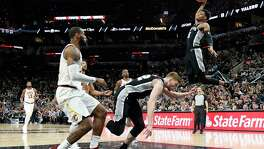 SAN ANTONIO,TX - JANUARY 23 :  Dejounte Murray #5 of the San Antonio Spurs dunks as LeBron James #23 of the Cleveland Cavaliers looks on at AT&T Center on January 23, 2018  in San Antonio, Texas.  NOTE TO USER: User expressly acknowledges and agrees that , by downloading and or using this photograph, User is consenting to the terms and conditions of the Getty Images License Agreement.