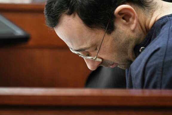 Larry Nassar hangs his head as former gymnast Amanda Thomashow gives her victim statement Tuesday, Jan. 23, 2018,  in Ingham County Circuit Court in Lansing, Mich. Nassar, 54, has admitted sexually assaulting athletes under the guise of medical treatment when he was employed by Michigan State University and USA Gymnastics, which as the sport's national governing organization trains Olympians. He already has been sentenced to 60 years in prison for child pornography. Under a plea bargain, he faces a minimum of 25 to 40 years behind bars in the molestation case.  (Matthew Dae Smith/Lansing State Journal via AP)