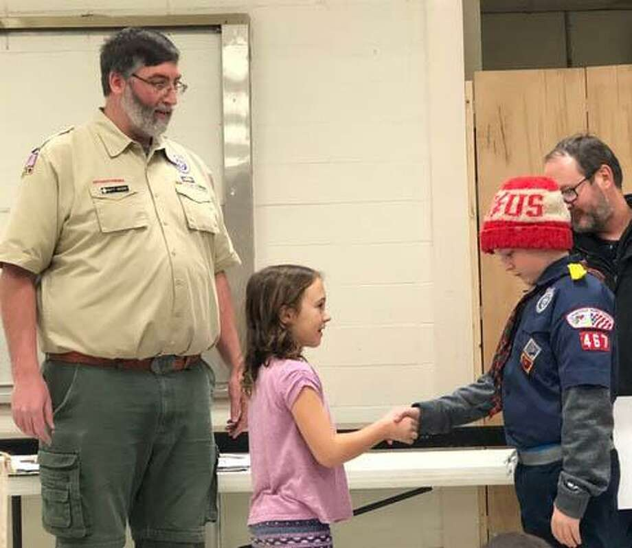 Lilah Reguin, 8, of New Milford is introduced to the Boy Scout handshake by her brother, Ian, an Arrow of Light, after she is received by the pack as the first female Cub Scout in the Northwest Hills district, Connecticut Rivers Council and in the state. Photo: Deborah Rose / Hearst Connecticut Media / Deo