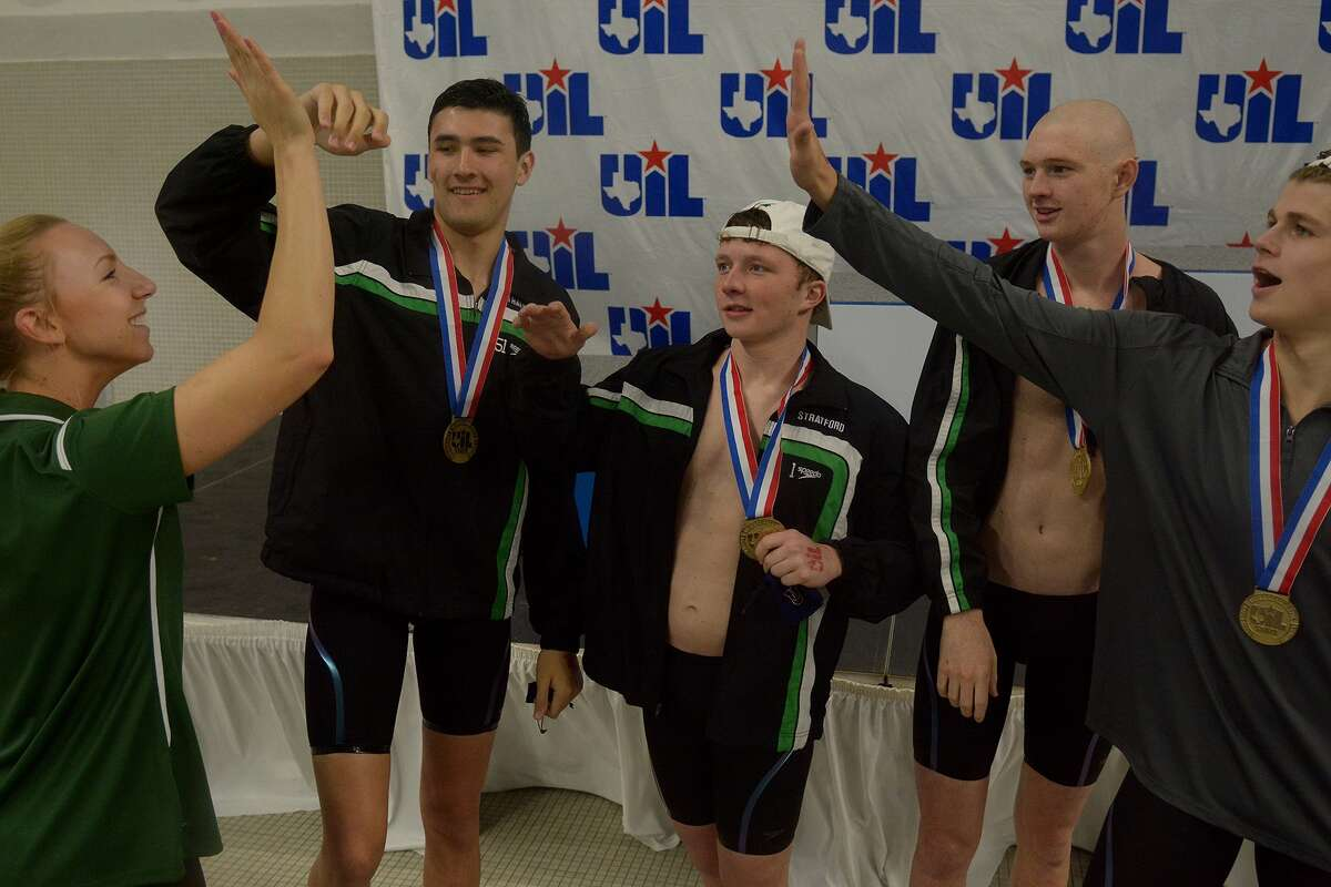 Stratford asst. swim coach Casie Burleigh, front left, gets a high five from sophomore Clayton Bobo, right, backed up by teammates junior Jim Nantz, from back left, sophomore Peyton Moak, and sophomore Cory Stephenson, after they received their gold medals for winning the conference 5A Boys 200 Yard Medley Relay championship final during the conference 5A 2016 UIL State Swimming and Diving Championships at the Texas Swim Center in Austin on Feb. 20, 2016. (Photo by Jerry Baker/Freelance)