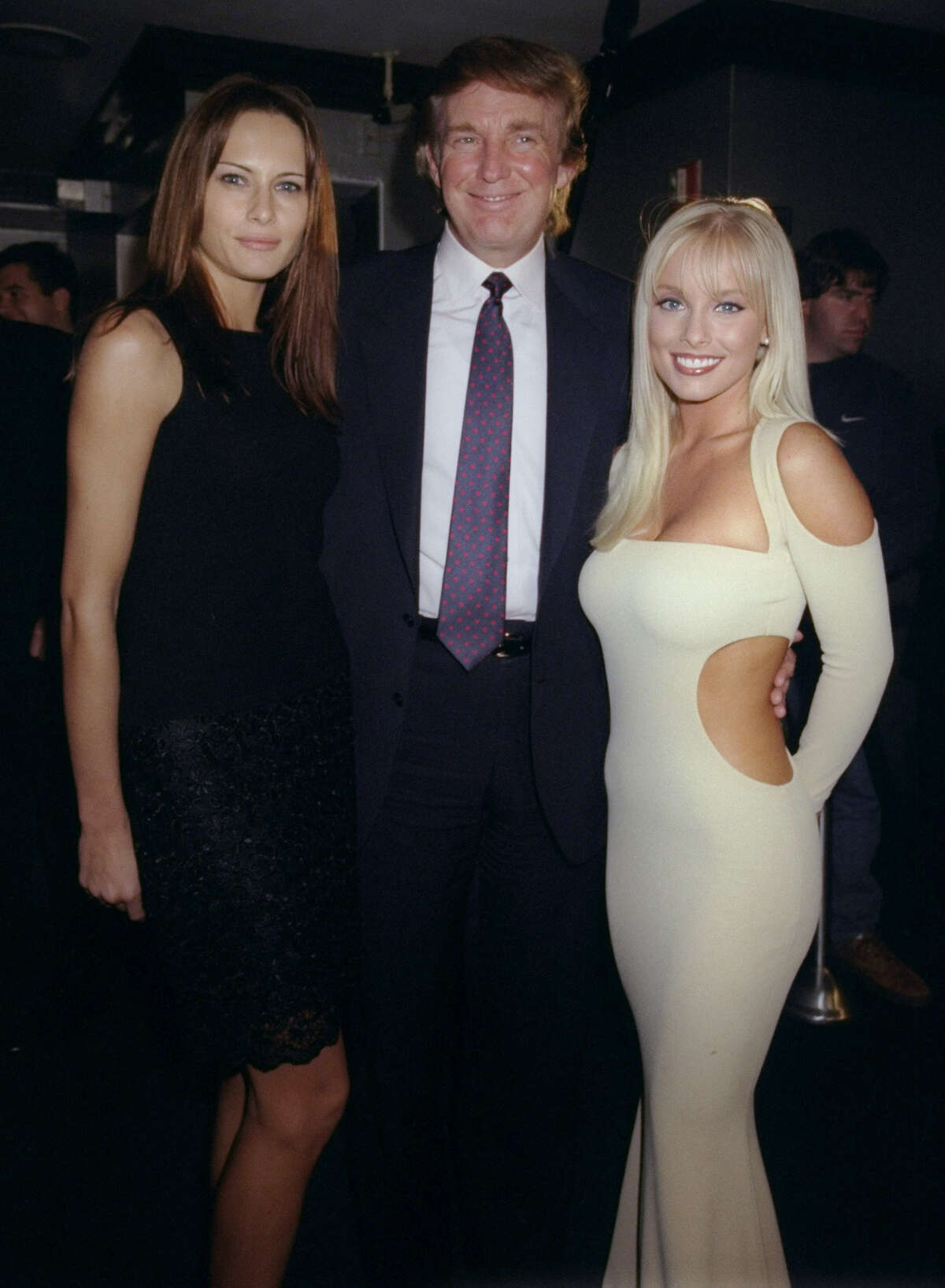 Donald Trump is flanked by his date, model Melania Knausss, and Jaime Bergman at a party celebrating Playboy magazine's 45th anniversary at the Life Club.