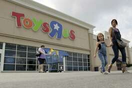 Shoppers leave a Toys R Us store, Tuesday, Sept. 19, 2017, in San Antonio. Toys R Us has filed for Chapter 11 bankruptcy protection while continuing with normal business operations.