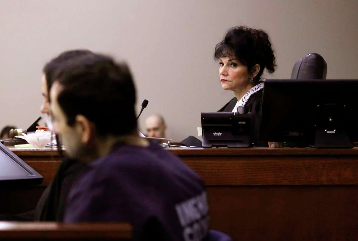 Judge Rosemarie Aquilina looks towards Larry Nassar as a victim gives her impact statement during the seventh day of Larry Nassar's sentencing hearing Wednesday, Jan. 24, 2018, in Lansing, Mich. Nassar has admitted sexually assaulting athletes when he was employed by Michigan State University and USA Gymnastics, which is the sport's national governing organization and trains Olympians. (AP Photo/Carlos Osorio)