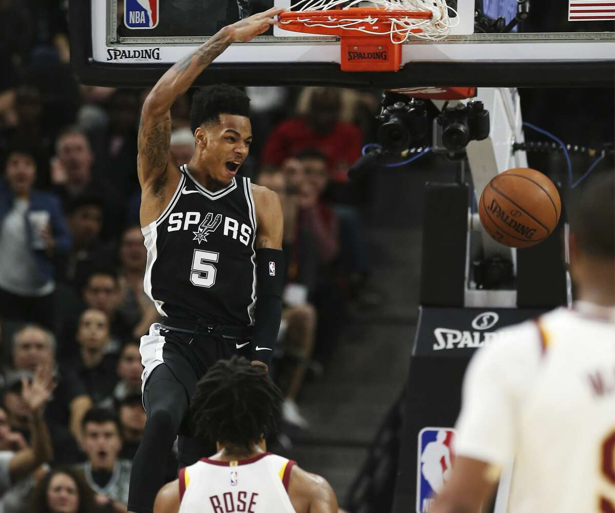 Spurs' Dejounte Murray (05) puts down a dunk against Cleveland Cavaliers' Derrick Rose (01) at the AT&T Center on Tuesday, Jan. 23, 2018. Spurs defeated the Cavs, 114-102. (Kin Man Hui/San Antonio Express-News)