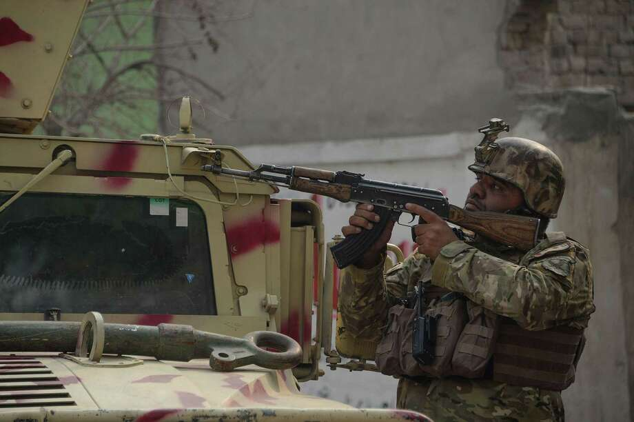 An Afghan army soldier takes position near an office of the British charity Save the Children during an ongoing attack in Jalalabad on January 24, 2018. Gunmen blasted their way into Save the Children's office in Afghanistan's restive east on January 24, witnesses and officials said, killing at least two people and wounding 14 others, in the latest attack on a foreign aid group in the war-torn country. Photo: Noorullah Shirzada / AFP /Getty Images / AFP or licensors