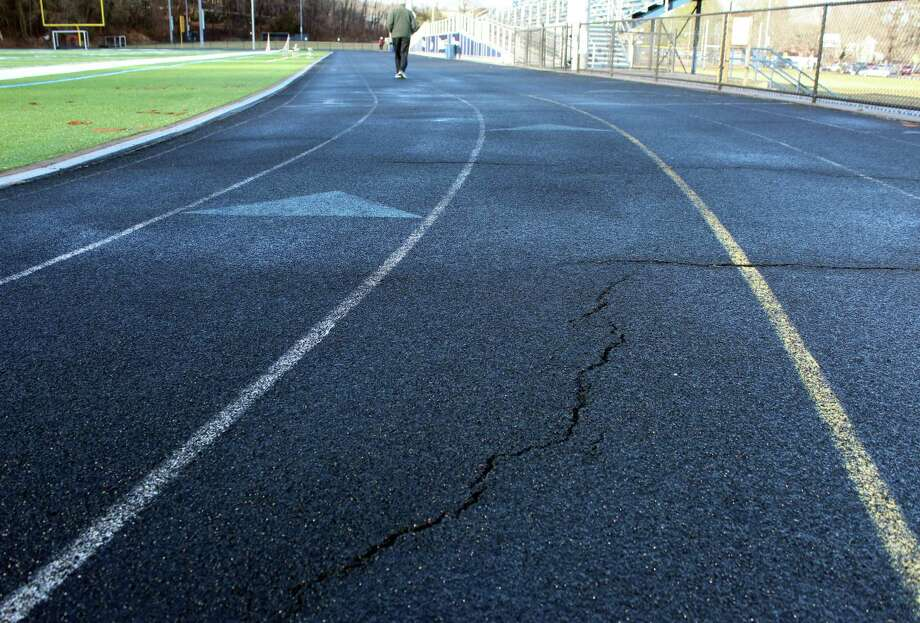 Cracks seen at the Wilton High School track, which is maintained by the town. Photo: Stephanie Kim / Hearst Connecticut Media