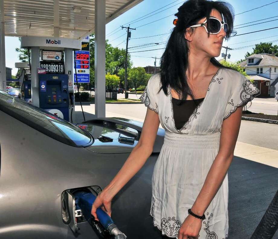 Saqiba Qasimi of Delmar fuels  up her car at Campus Mobil on Western Avenue in Albany Wednesday morning as Capital Region prices decine.  Some experts say the trend will continue, but world events could boost prices.  (John Carl D'Annibale / Times Union) Photo: John Carl D'Annibale