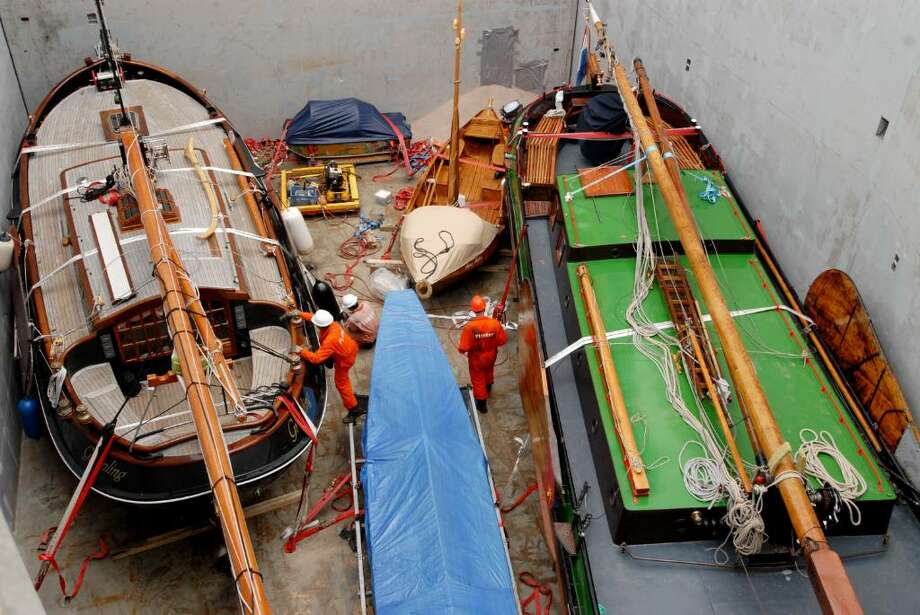 Dutch flat-bottomed sailing yachts at the Port of Albany are loaded Monday, Oct. 5, aboard the transport vessel Flinterborg, which will take them back to Harlingen in the Netherlands. The flotilla was brought to New York to commemorate the 400th anniversary of Henry Hudson?s exploration that led to the region?s first European settlements. The boat loading continue Tuesday. (Will Waldron / Times Union) / 00005806A