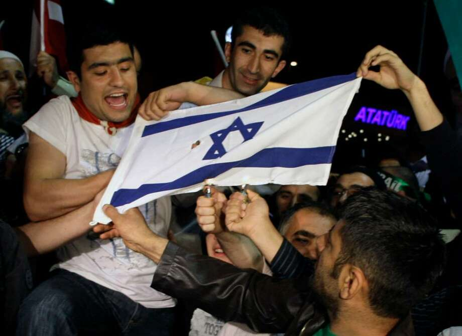 Friends and family members of Turkish activists who were deported by Israel two days after a deadly naval raid by Israeli forces in the Mediterranean Sea,  set on fire an Israeli flag as they wait at Ataturk Airport in Istanbul, Turkey,  early Thursday, June 3, 2010. Hundreds of activists deported from Israel following a bloody raid by Israeli commandos on a pro-Palestinian flotilla returned to a hero's welcome in Turkey early Thursday. (AP Photo/Ibrahim Usta) Photo: Ibrahim Usta / AP