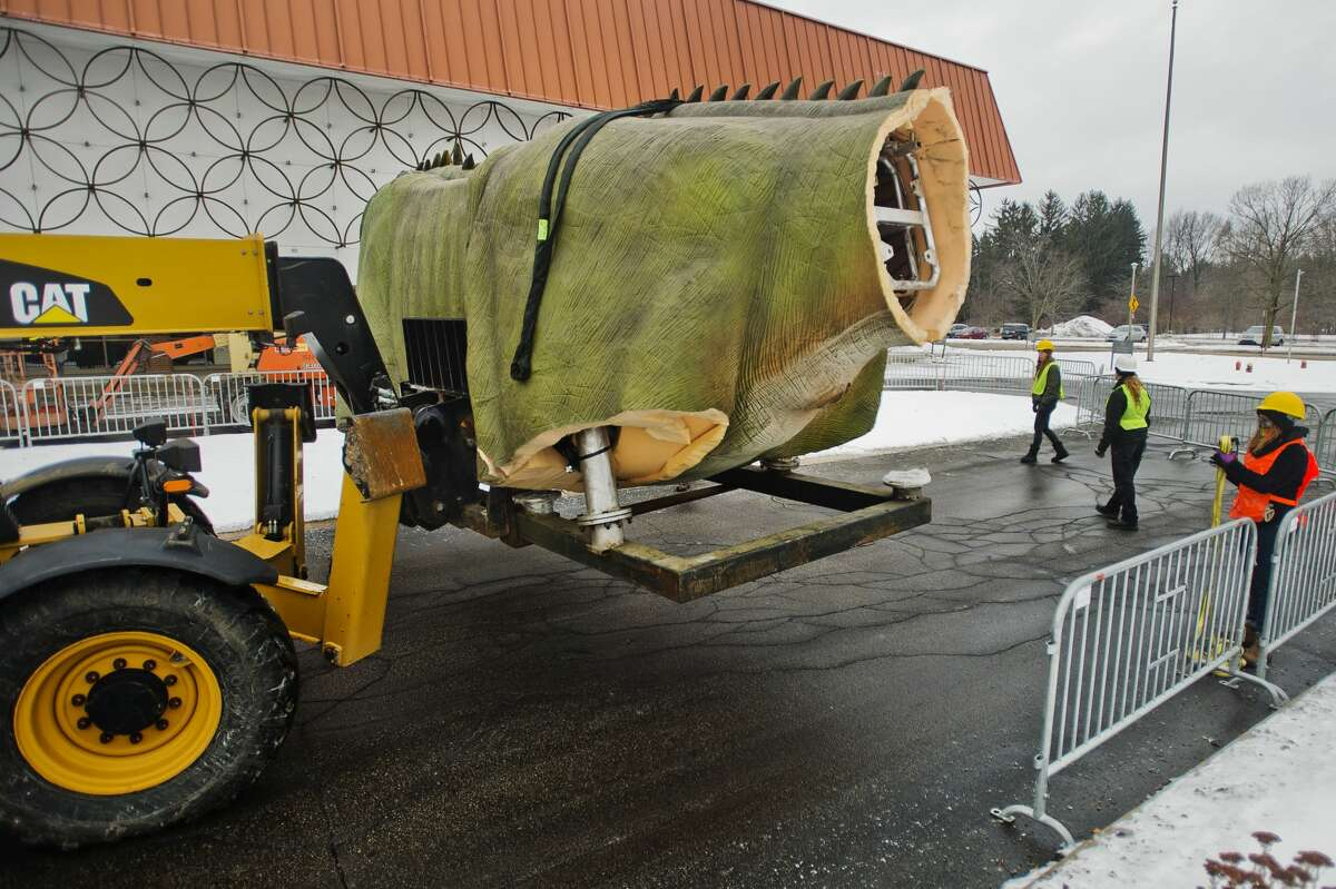 Workers install a large animatronic dinosaur in front of the Midland Center for the Arts on Tuesday, Jan. 18, 2018. The brachiosaurus is part of a new exhibition called