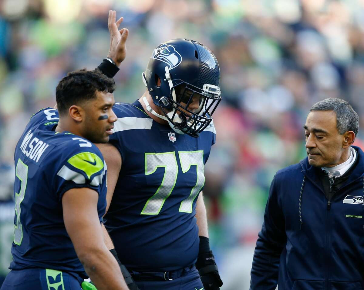 SEATTLE, WA - DECEMBER 31: Quarterback Russell Wilson #3 of the Seattle Seahawks walks with teammate Ethan Pocic #77 after Pocic sustained an injury in the first half against the Arizona Cardinals at CenturyLink Field on December 31, 2017 in Seattle, Washington. (Photo by Otto Greule Jr /Getty Images)