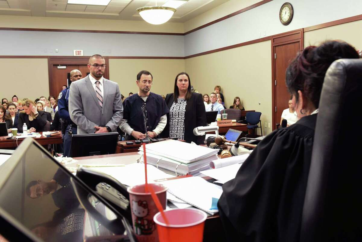 """Larry Nassar faces Ingham County Circuit Judge Rosemarie Aquilina prior to his sentencing Wednesday, Jan. 24, 2018, after the seventh day of victim impact statements in Ingham County Circuit Court in Lansing, Mich. The former sports doctor who admitted molesting some of the nation's top gymnasts for years was sentenced Wednesday to 40 to 175 years in prison as Aquilina declared: """"I just signed your death warrant."""" The sentence capped a remarkable seven-day hearing in which scores of Nassar's victims were able to confront him face to face in the Michigan courtroom. (Matthew Dae Smith/Lansing State Journal via AP)"""