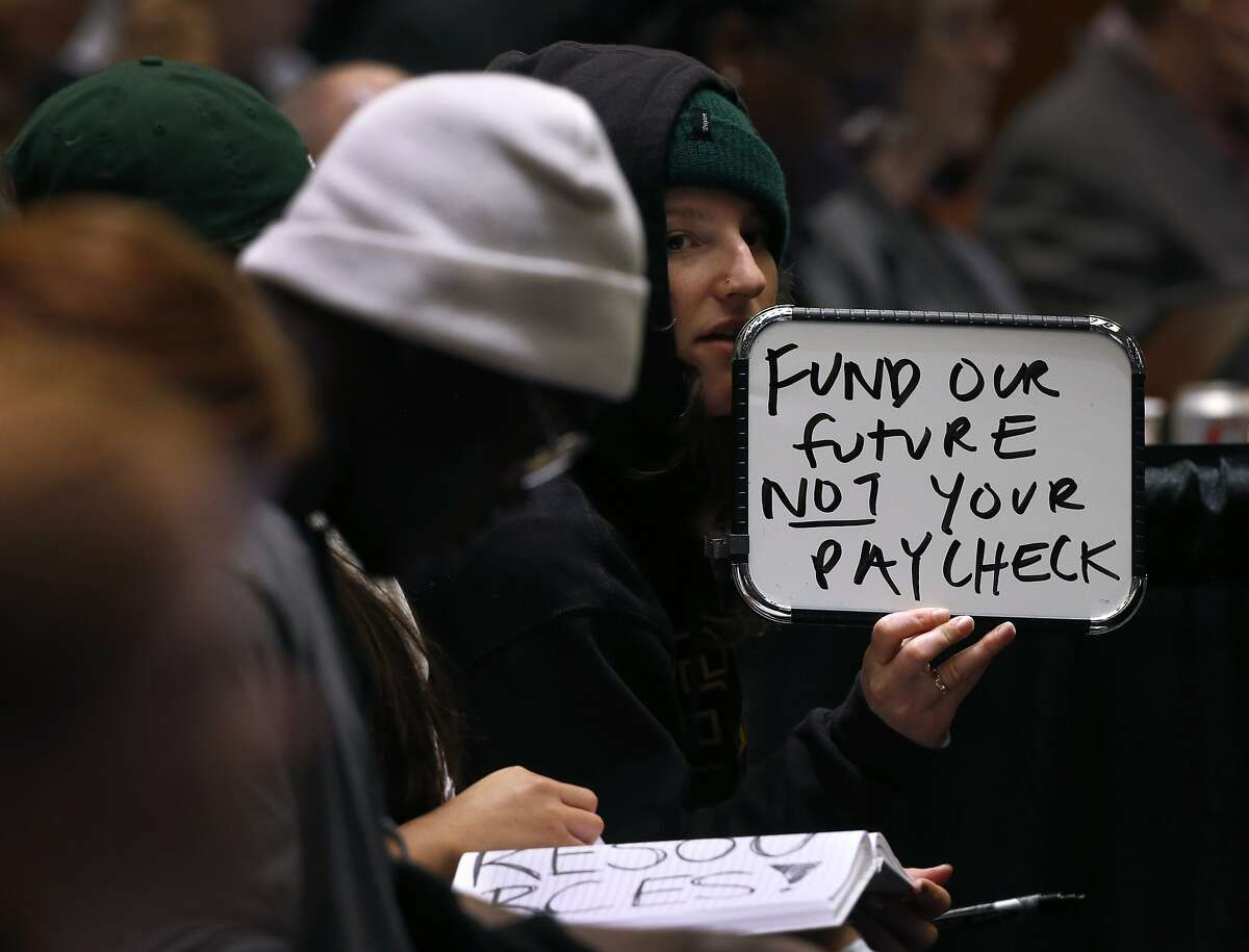 UC Santa Cruz student Katherine Wethington holds a white board to display a message at a meeting of the UC Board of Regents in San Francisco, Calif. on Wednesday, Jan. 24, 2018 where a tuition increase is being considered.