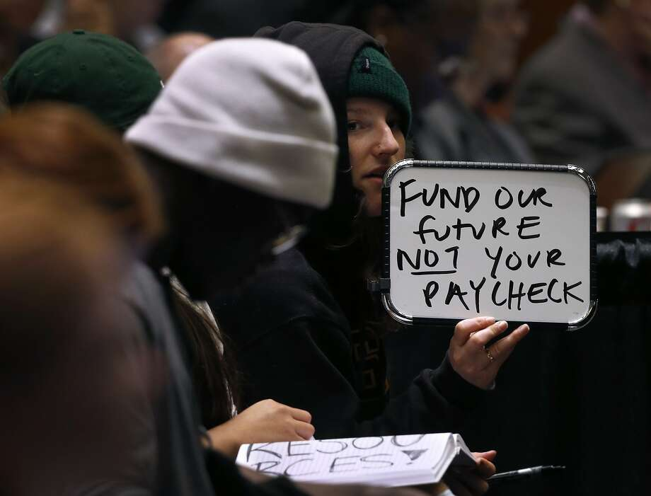 UC Santa Cruz student Katherine Wethington holds a white board to display a message at a meeting of the UC Board of Regents in San Francisco, Calif. on Wednesday, Jan. 24, 2018 where a tuition increase is being considered. Photo: Paul Chinn / The Chronicle