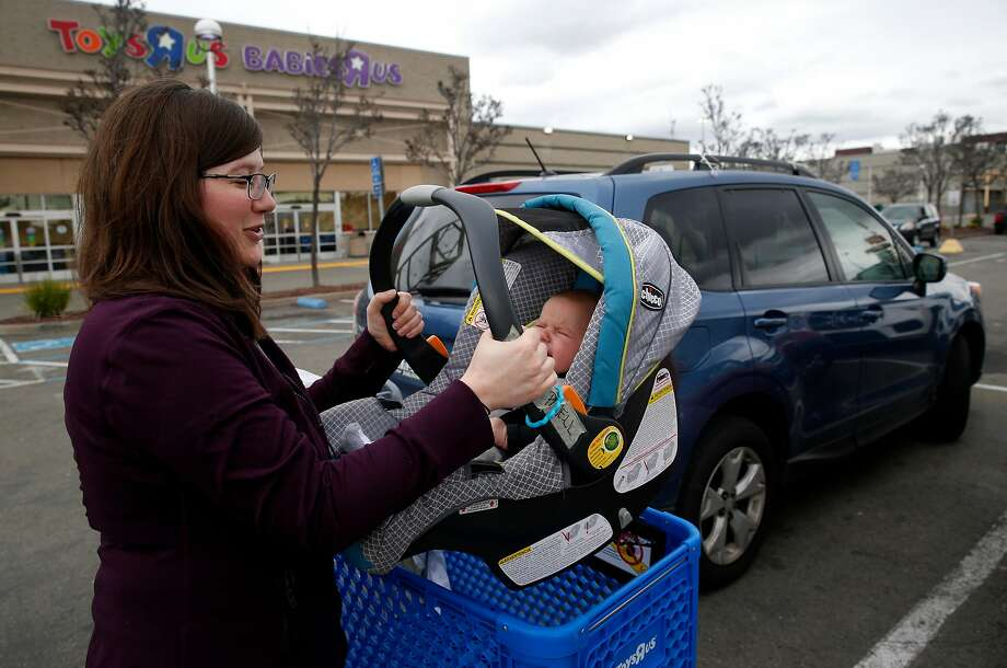 Mychal Powell carries daughter Clementine to their car after shopping at the Toys R Us store in Emeryville, which is closing. Photo: Paul Chinn, The Chronicle