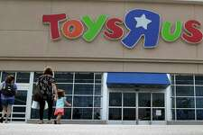 FILE - In this Sept. 19, 2017, file photo, shoppers walk into a Toys R Us store, in San Antonio. Toys R Us says it will be closing some U.S. stores and converting others to cobranded locations as it continues to deal with its financial restructuring following its bankruptcy filing. (AP Photo/Eric Gay, File)