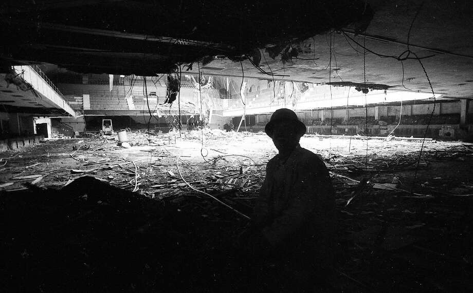 A worker in the shadows looks at the interior of the Winterland Ballroom during its demolition in 1985. Photo: Tom Levy, The Chronicle