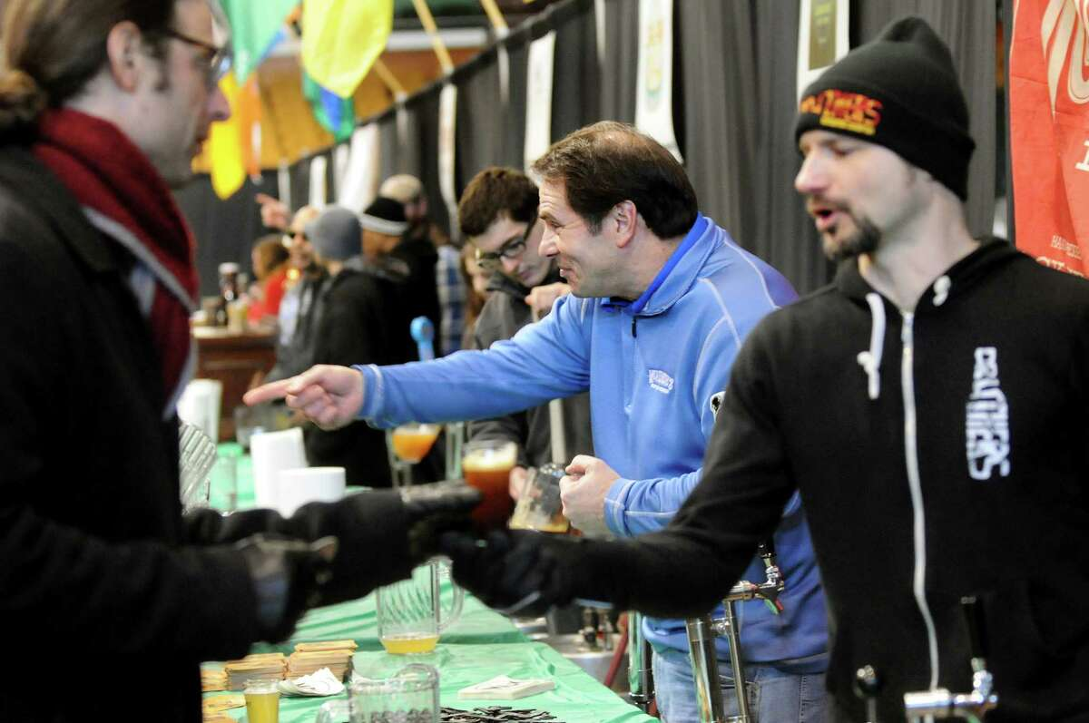 Craft brewery workers, including regional sales manager Rick Yandoli of McKenzie's Hard Cider, center, serve their specialty beverages during the Albany Winter Brewfest on Saturday, Feb. 8, 2014, at the Washington Avenue Armory in Albany, N.Y. (Cindy Schultz / Times Union)