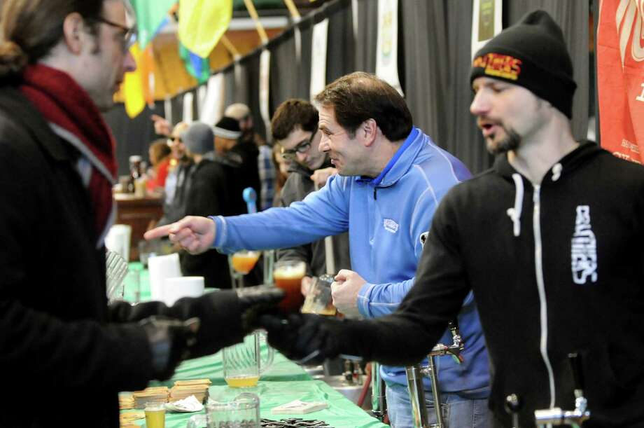 Craft brewery workers, including regional sales manager Rick Yandoli of McKenzie's Hard Cider, center, serve their specialty beverages during the Albany Winter Brewfest on Saturday, Feb. 8, 2014, at the Washington Avenue Armory in Albany, N.Y. (Cindy Schultz / Times Union) Photo: Cindy Schultz / 00025607A