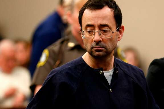 """Former Michigan State University and USA Gymnastics doctor Larry Nassar addresses the court during the sentencing phase in Ingham County Circuit Court on January 24, 2018 in Lansing, Michigan.  Disgraced former USA Gymnastics doctor Larry Nassar was sentenced to 40 to 175 years in prison on Wednesday for sexually abusing scores of young girls under the guise of medical treatment. """"I've just signed your death warrant,"""" Judge Rosemarie Aquilina said as she handed down the sentence after a week of gut-wrenching testimony by over 150 of Nassar's victims.  / AFP PHOTO / JEFF KOWALSKYJEFF KOWALSKY/AFP/Getty Images"""