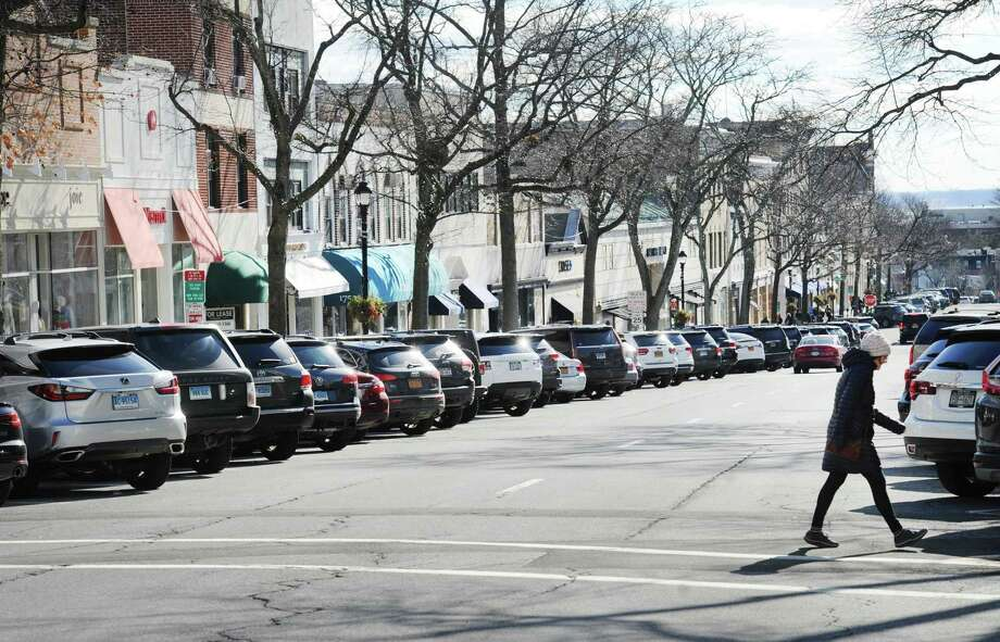 All the parking spots on Greenwich Avenue are filled as a pedestrian crosses in the Lewis Street crosswalk in Greenwich. Photo: Bob Luckey Jr. / Hearst Connecticut Media / Greenwich Time