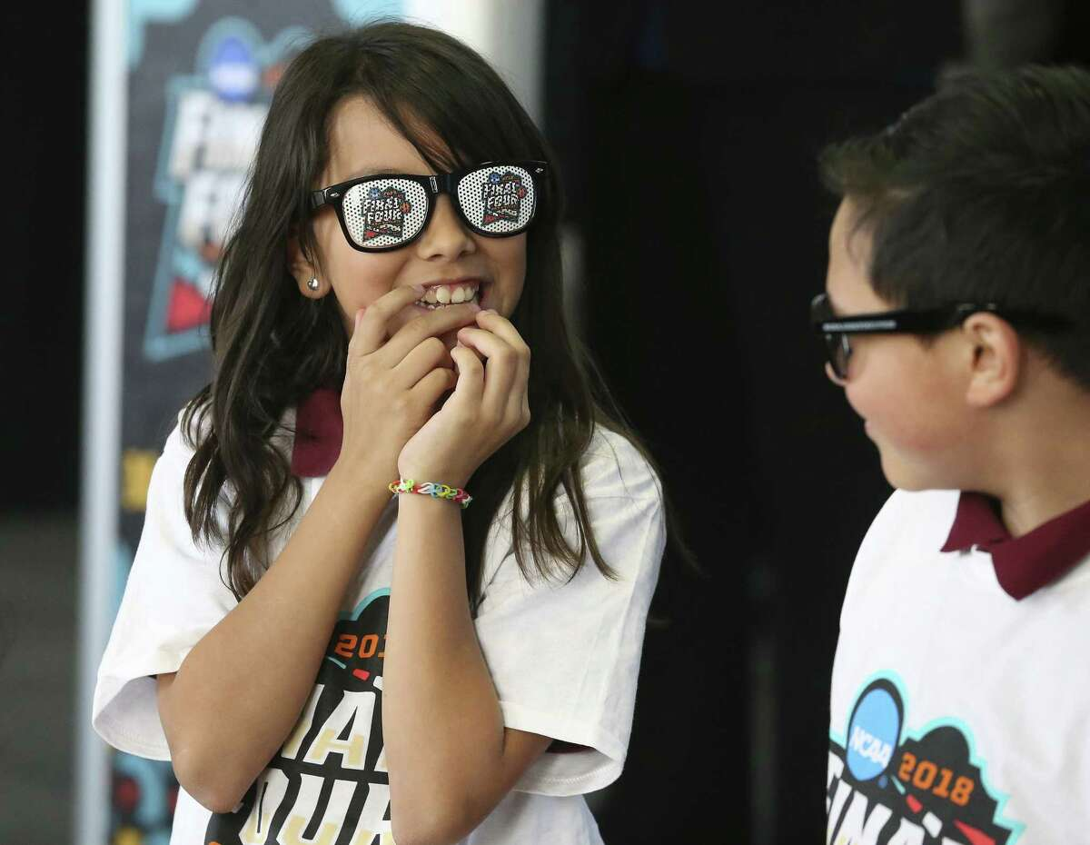 Alina Vega giggles as she and Brian Ybarra put on Final Four glasses after leaders gather at Higgs Carter & King School gymnasium to announce key details for the NCAA Final Four Legacy Project on January 24, 2018.