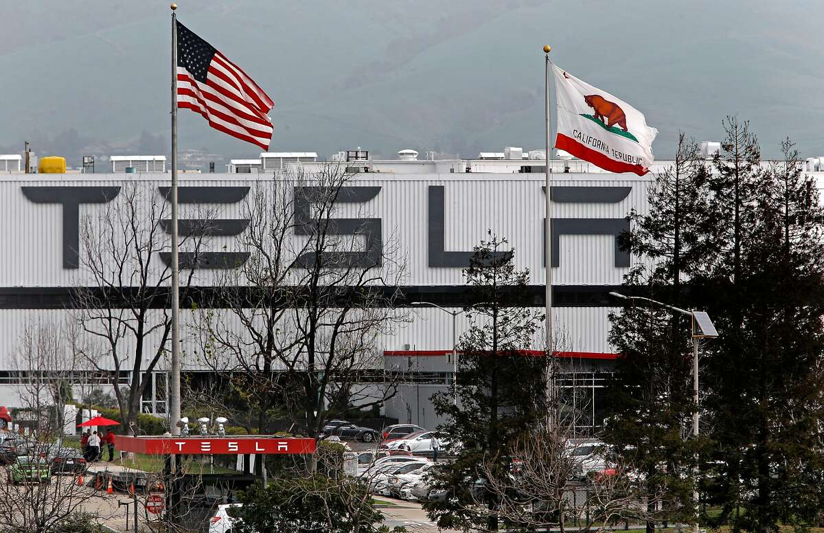 The United States and the State of California flags fly in front of Tesla Motors, California's only full-scale auto manufacturing plant in Fremont, Calif. as seen on Thurs. Feb. 19, 2015.