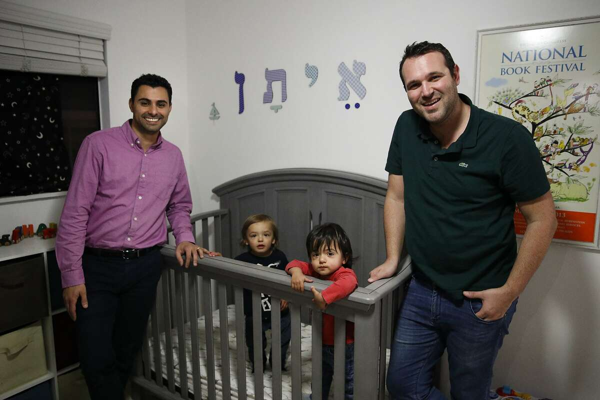 Elad Dvash-Banks, left, and his partner, Andrew, pose for photos with their twin sons, Ethan, center right, and Aiden in their apartment Tuesday, Jan. 23, 2018, in Los Angeles. The twins share almost everything: the same toys, the same nursery, the clothes and the same parents. Everything but a toothbrush and U.S. citizenship. Ethan became a plaintiff in a federal lawsuit against the U.S. State Department that seeks the same rights his brother has as a citizen. (AP Photo/Jae C. Hong)