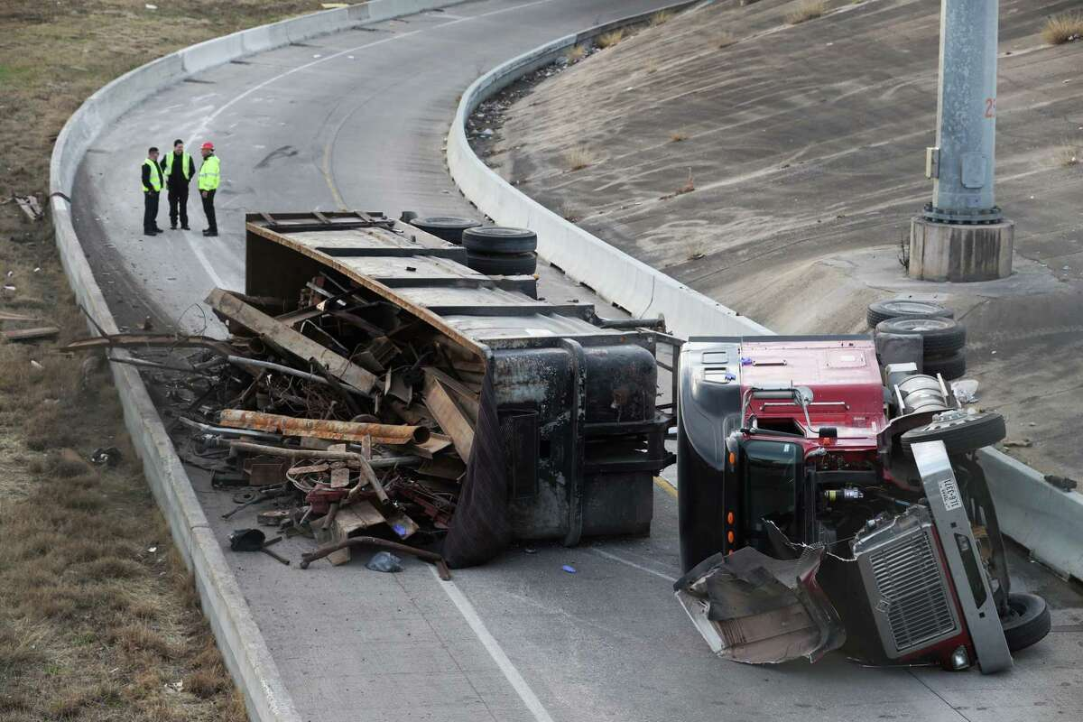 Authorities investigate an 18-wheeler accident on the entrance ramp to Interstate 10 near downtown Houston Tuesday, Jan. 23. The big rig initially reported as having fallen off a highway overpass actually rolled over after taking a turn too fast, the Houston Police Department said. ( Jon Shapley / Houston Chronicle )