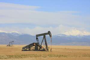 A Pumpjack pumping oil from an oil well in the plains with snow capped mountains in the backgroud.      oil wells, industry, gas, gasoline, pump, mountains, plains, pumpjack,  nodding donkey, pumping unit, horsehead pump, borehole, fuel, natural gas, crude, crisis, beam pump, rod pump, grasshopper, thirsty bird, jack pump, drilling, gusher,  production, petroleum, reserve