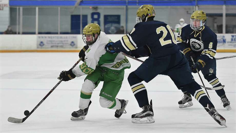 Notre Dame-West Haven junior forward Tom Ashmore gains control of a loose puck battling Notre Dame-Fairfield sophomore defenseman Matt Ward (20) and senior captain Chris Becker (9), Wednesday, Jan. 24, 2018, at Bennett Rink in West Haven. Notre Dame-West Haven won, 5-0. Photo: Catherine Avalone, Hearst Connecticut Media / New Haven Register