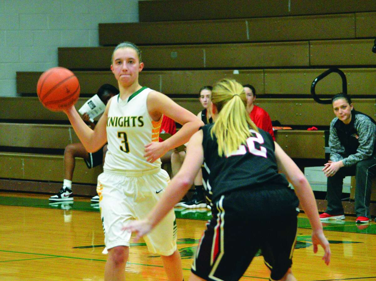 Metro-East Lutheran junior Sami Kasting, left, looks to pass the ball during Wednesday's consolation quarterfinal against Granite City at the Carrollton Lady Hawk Invitational.