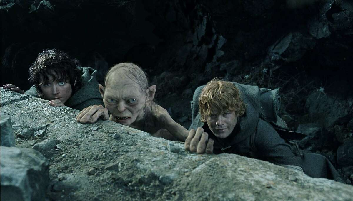 Frodo (Elijah Wood), Gollum(Andy Serkis) and Sam (Sean Astin) take cover as they plot to enter Mount Doom in New Line Cinema's epic film,