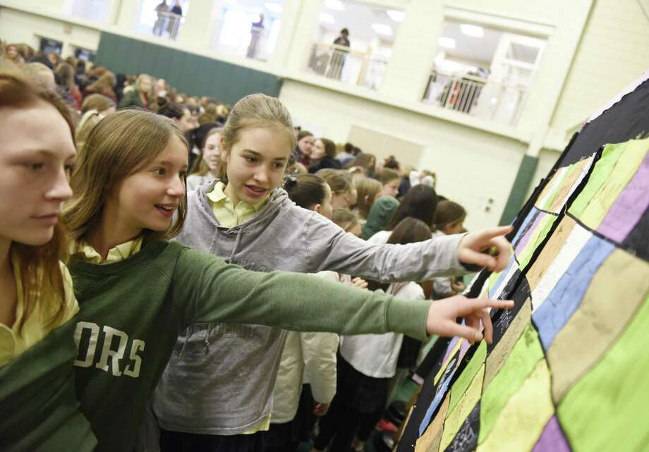 """Greenwich Academy Sixth-graders Giselle Messina, left, Dasha Scaminaci, center, and Phelan Bryant look at unique patches on a collaboratve quilt at the """"Beloved Community"""" assembly and quilt presentation at Greenwich Academy in Greenwich, Conn. Thursday, Jan. 25, 2018. Students and faculty at G.A. contributed patches to make a collaborative quilt reflecting Dr. King's message. Student's watched a video of MLK's """"I Have a Dream"""" speech and sang songs before a packed gym. Photo: Tyler Sizemore / Hearst Connecticut Media / Greenwich Time"""