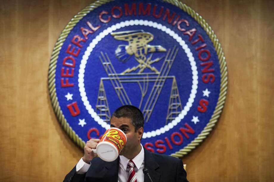 Ajit Pai, chairman of the Federal Communications Commission (FCC), drinks from an oversized coffee mug during a meeting in Washington on Nov. 16, 2017. Photo: Bloomberg Photo By Zach Gibson. / © 2017 Bloomberg Finance LP