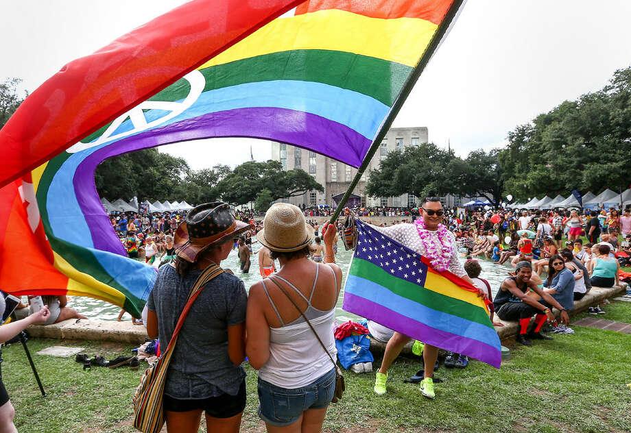 A couple stands under a rainbow flag at the 2016 Houston Pride festival. (Jon Shapley/Houston Chronicle)