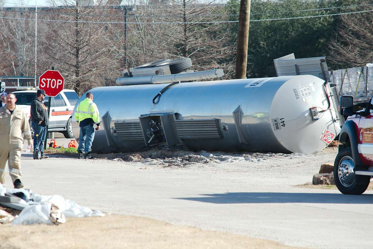 Police officers and cleanup workers report to the scene of an overturned tanker truck on Winkler near Highway 3 in South Houston Thursday, Jan 25.