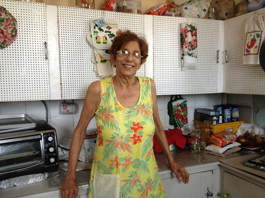 "Victoria Ramessar, or ""Auntie Doll"" to her family, is pictured in her kitchen in San Fernando, Trinidad, the last time she cooked for her family. Photo: Linda Shiue"