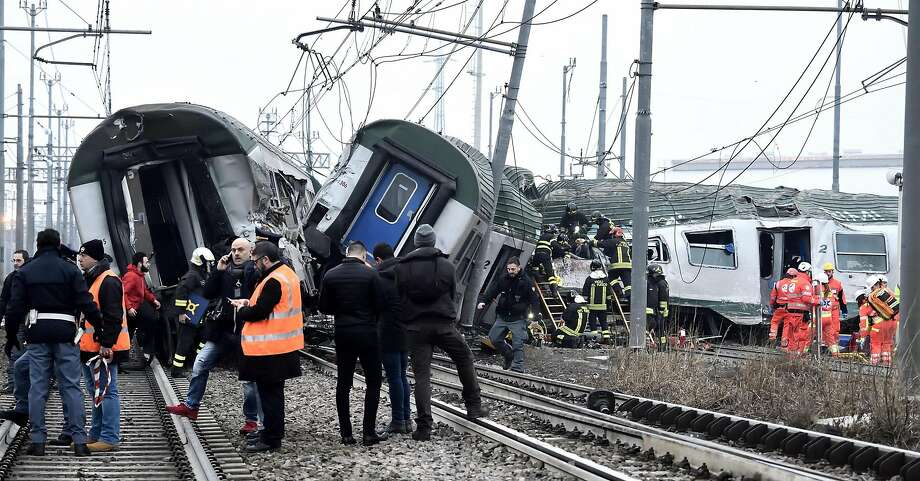 Rescue teams help passengers out of a derailed commuter train on the outskirts of Milan, Italy. Photo: Flavio Loscalzo, Associated Press