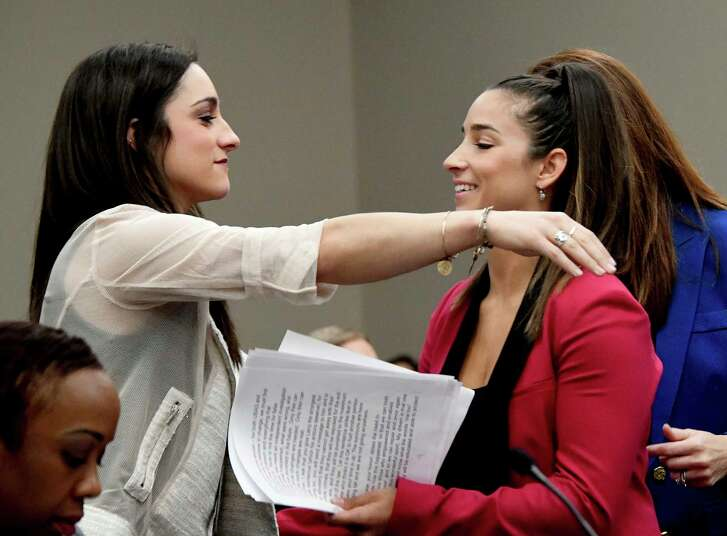 Olympic gold medalists Aly Raisman, right, and Jordyn Wieber embrace during victim impact statements, Friday, Jan. 19, 2018, in Lansing, Mich., during the fourth day of sentencing for former sports doctor Larry Nassar, who pled guilty to multiple counts of sexual assault.  (Dale G. Young/Detroit News via AP)