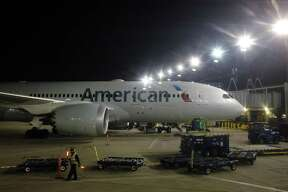 An American Airlines plane is parked at a gate at O'Hare International Airport in Chicago. American Airlines Group Inc. reported Thursday that fourth-quarter profit slipped 11 percent as higher costs for fuel and labor offset rising revenue.