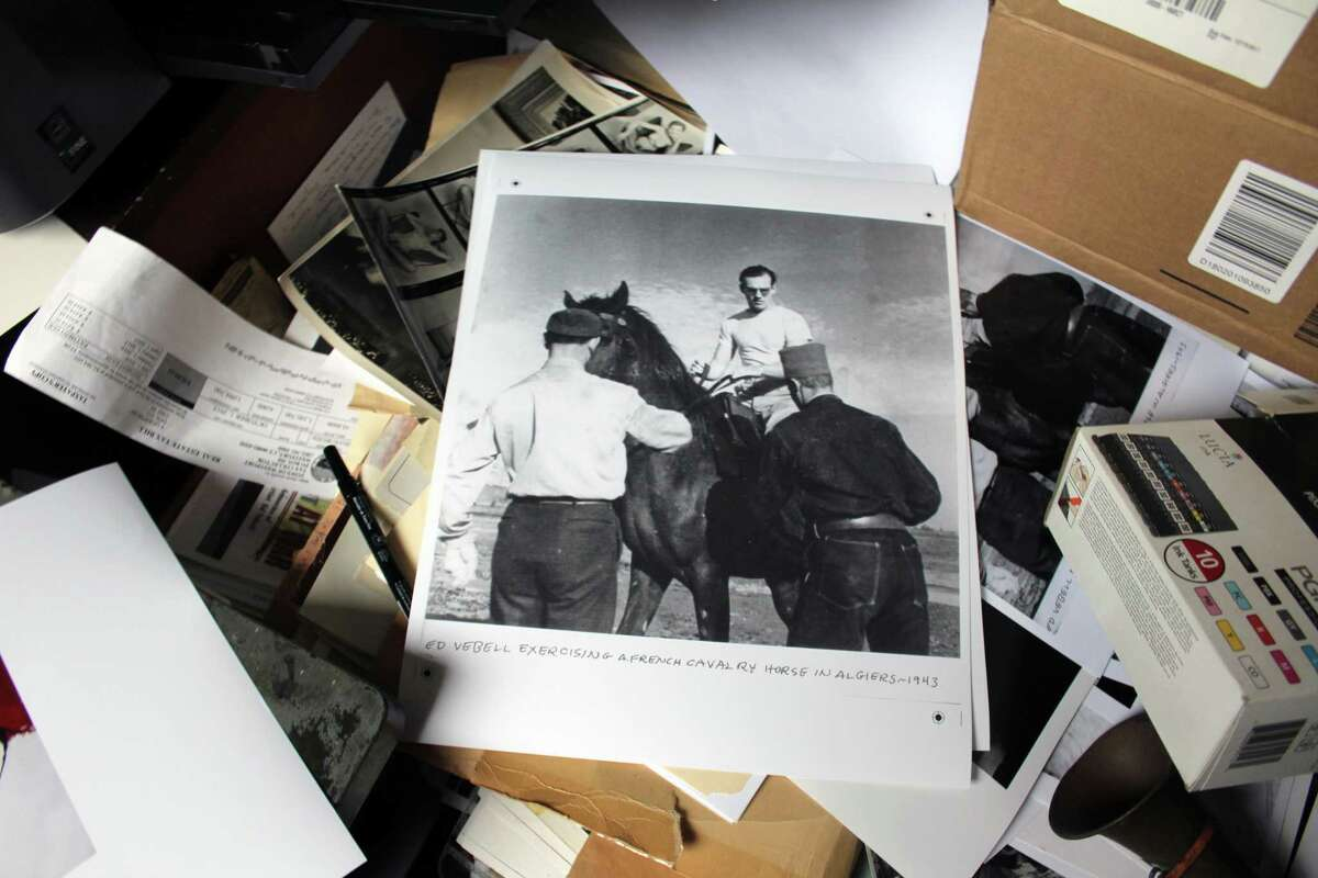 """An old photo on the desk of Ed Vebell's home office. The caption reads """"Ed Vebell exercising a French cavalry horse in Algiers - 1953."""" In Westport, Conn., Jan. 22, 2018."""