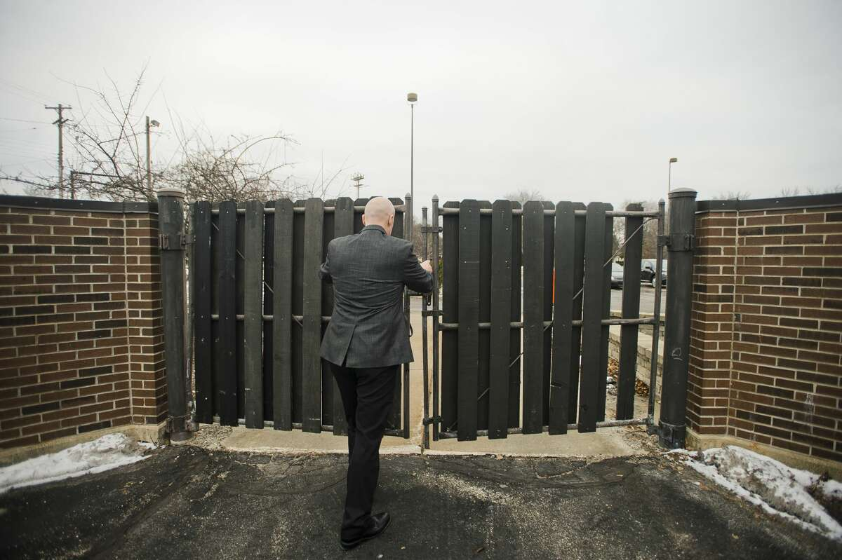 Midland Chief of Police Clifford Block closes a gate near the front of the Law Enforcement Center at 2727 Rodd St. on Thursday, Jan. 25, 2018. Renovations are planned for the facility, which will include new gates with added security surrounding one section of the parking lot. (Katy Kildee/kkildee@mdn.net)