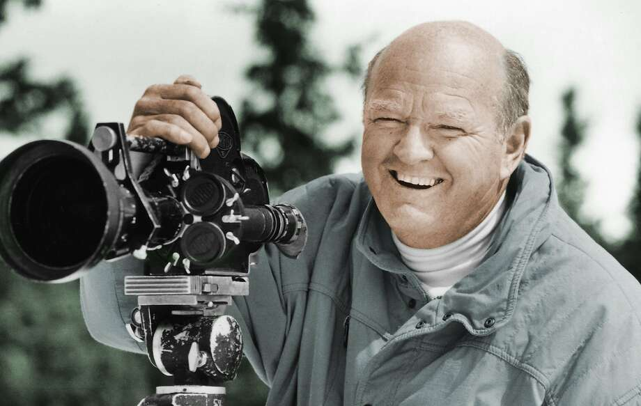 In this undated photo provided by the Warren Miller Co., Warren Miller is shown posing for a photo with a film camera. Miller, the prolific outdoor filmmaker who for decades made homages to the skiing life that he narrated with his own humorous style, died Wednesday, Jan. 24, 2018, at his home on Orcas Island, Wash., his family said. He was 93. A World War II veteran, ski racer, surfer and sailor, Miller produced more than 500 films on a variety of outdoor activities. However it was his ski films for which he was most known. (Warren Miller Co. via AP) Photo: Associated Press