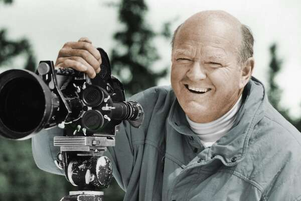 In this undated photo provided by the Warren Miller Co., Warren Miller is shown posing for a photo with a film camera. Miller, the prolific outdoor filmmaker who for decades made homages to the skiing life that he narrated with his own humorous style, died Wednesday, Jan. 24, 2018, at his home on Orcas Island, Wash., his family said. He was 93. A World War II veteran, ski racer, surfer and sailor, Miller produced more than 500 films on a variety of outdoor activities. However it was his ski films for which he was most known. (Warren Miller Co. via AP)